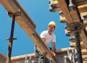 Authentic construction worker placing slab formwork beams in construction site