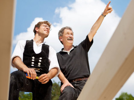 Close-up of two carpenters discussing the work on top of an unfinished roof